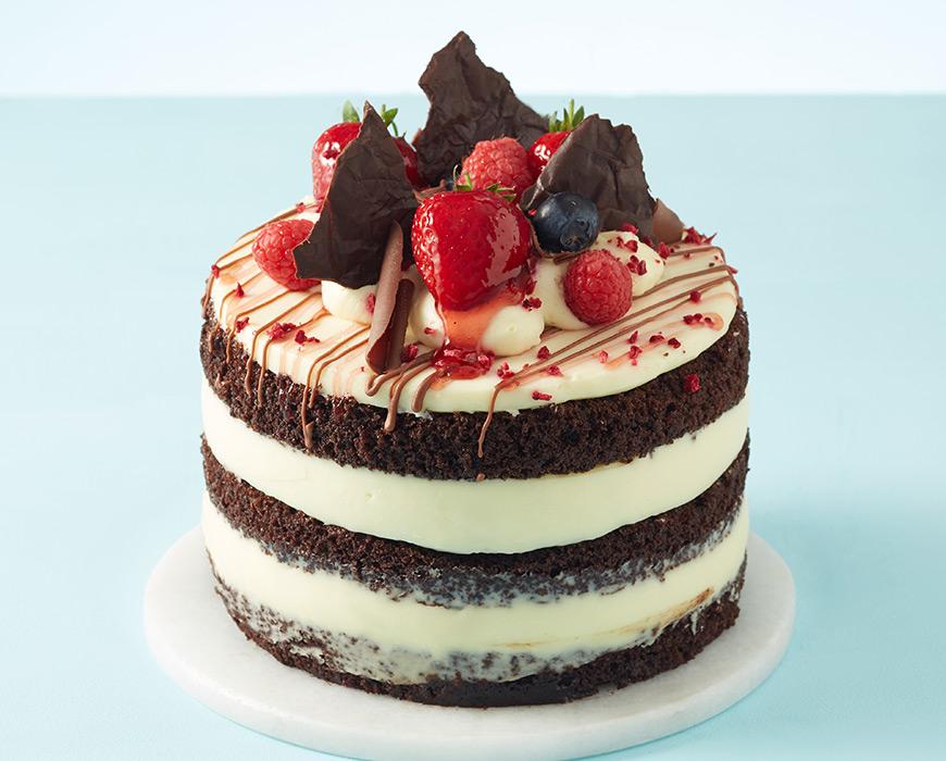 Naked chocolate and vanilla cake with fresh berries
